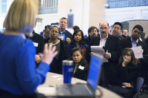 Job seekers listen to a social media expert explain how the networks can be used to find work during a job fair put on by online recruiting company TheLadders at Grand Central Station in New York