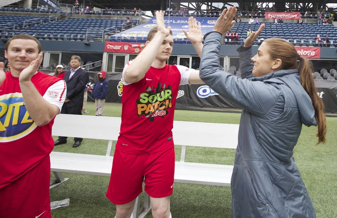 U.S. Soccer star Alex Morgan, far right, celebrates a goal while coaching a team comprised mostly of Seattle-area veterans during an exhibition soccer game at CenturyLink Field organized by the Official Snacks of U.S. Soccer (OREO, RITZ, TRIDENT, SOUR PATCH KIDS & HONEY MAID) in Seattle Wednesday April 23, 2014. The game replicated the thrills of a major international match for amateur players as part of the new #PassTheLove program to celebrate the spirit of soccer heading into the worldís largest sporting event this summer. (Stephen Brashear/AP Images for Mondelez International)