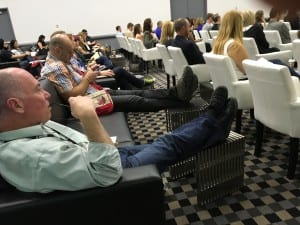 Attendees kick back and take notes from couches and lounge chairs in session rooms. Nice.