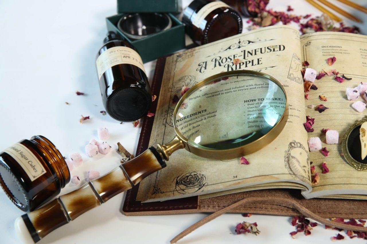 journal, magnifying glass, overturned bottles HBO The Nevers