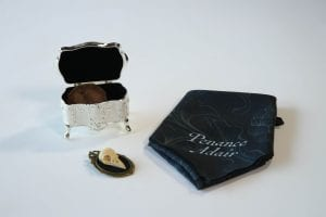 a Victorian-style trinket box, a vintage broach and an ornate handkerchief HBO The Nevers
