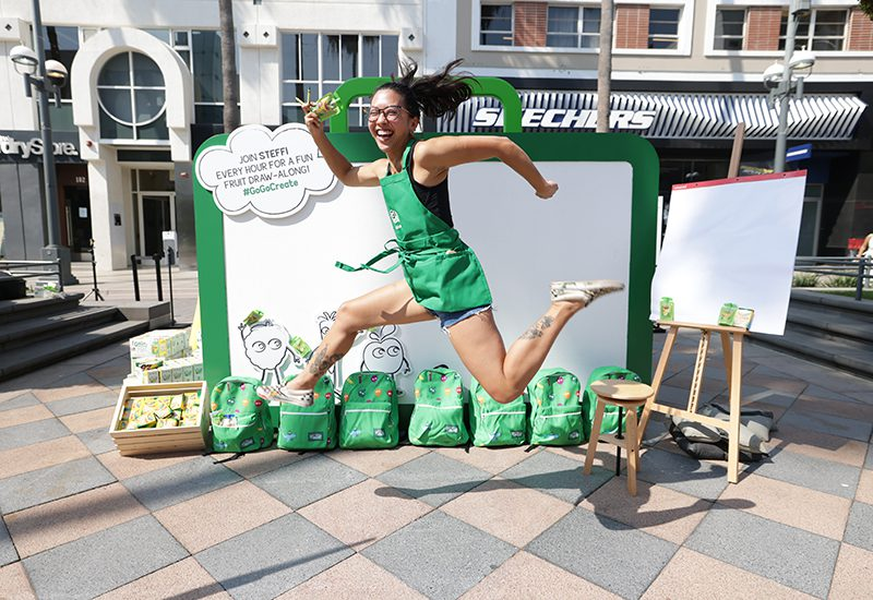 GoGo squeeZ x Crayola 2021_Woman jumping by green installation